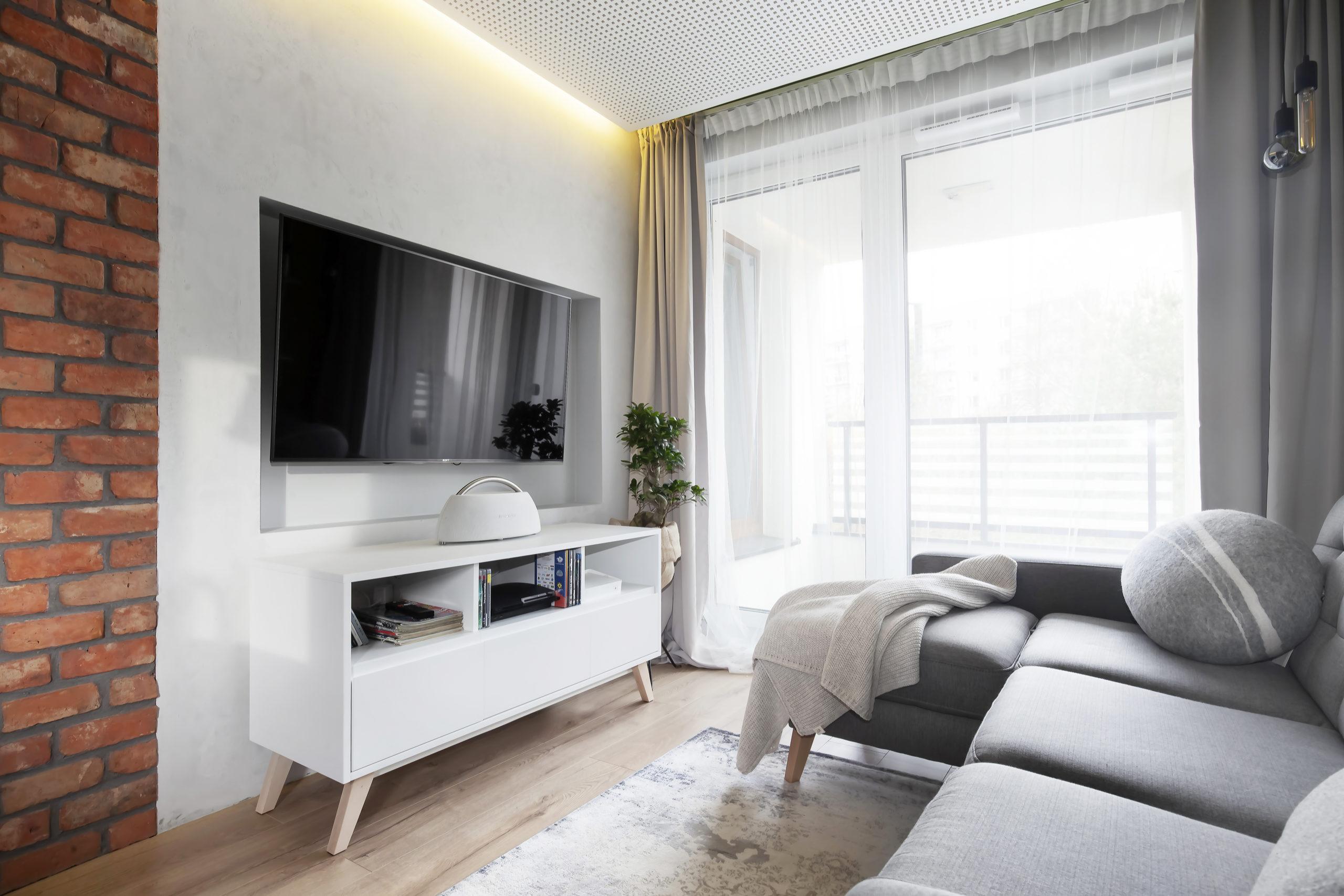 szara sofa i cegła w nowoczesnym salonie